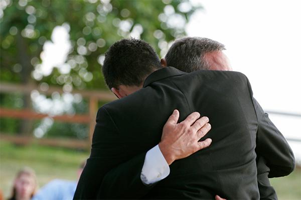 two men in suits hugging