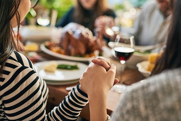 family-holding-hands-at-dinner