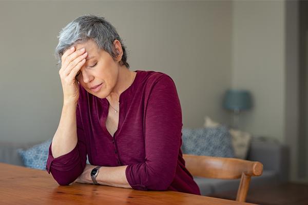 woman sitting holding head